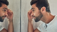 Shot of a confident young man looking at himself closely in the mirror at home during the day