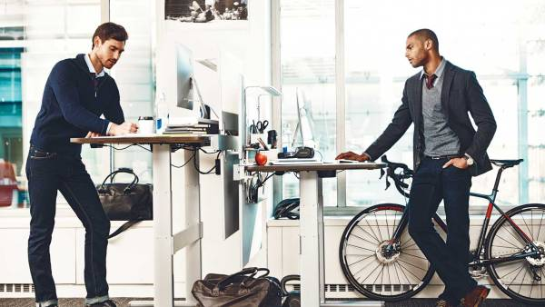 Young men at standing desks in office