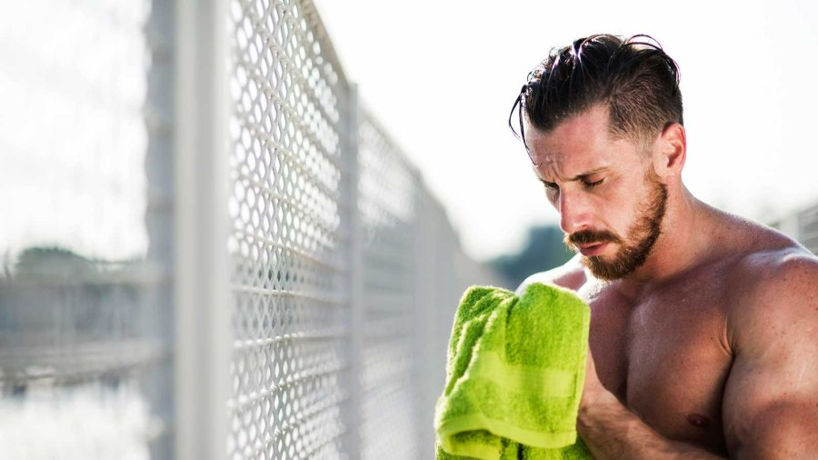 Runner wiping sweat off face