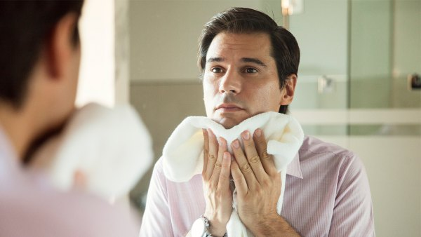 Man looking in mirror, drying his face with a towel