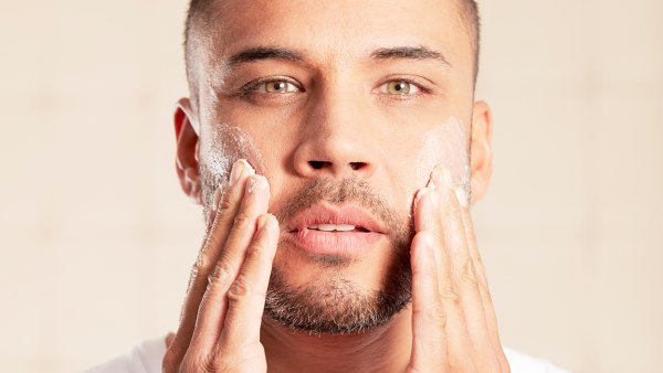 Portrait of mid adult man using skin care product.