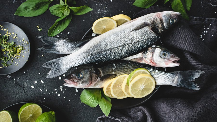Fresh fish with lemon, spices and herbs ready for cooking on dark background