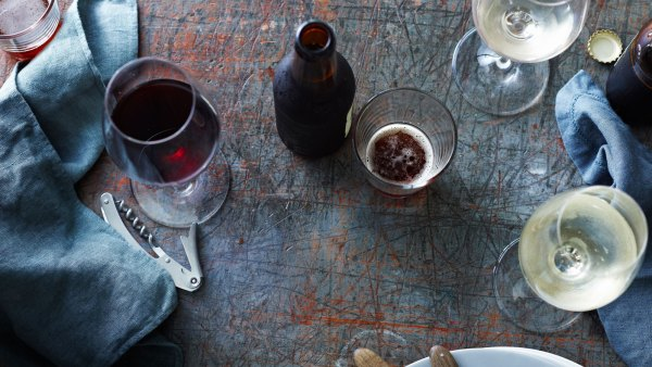 Bottled beer with red and white wine glasses on table, overhead view