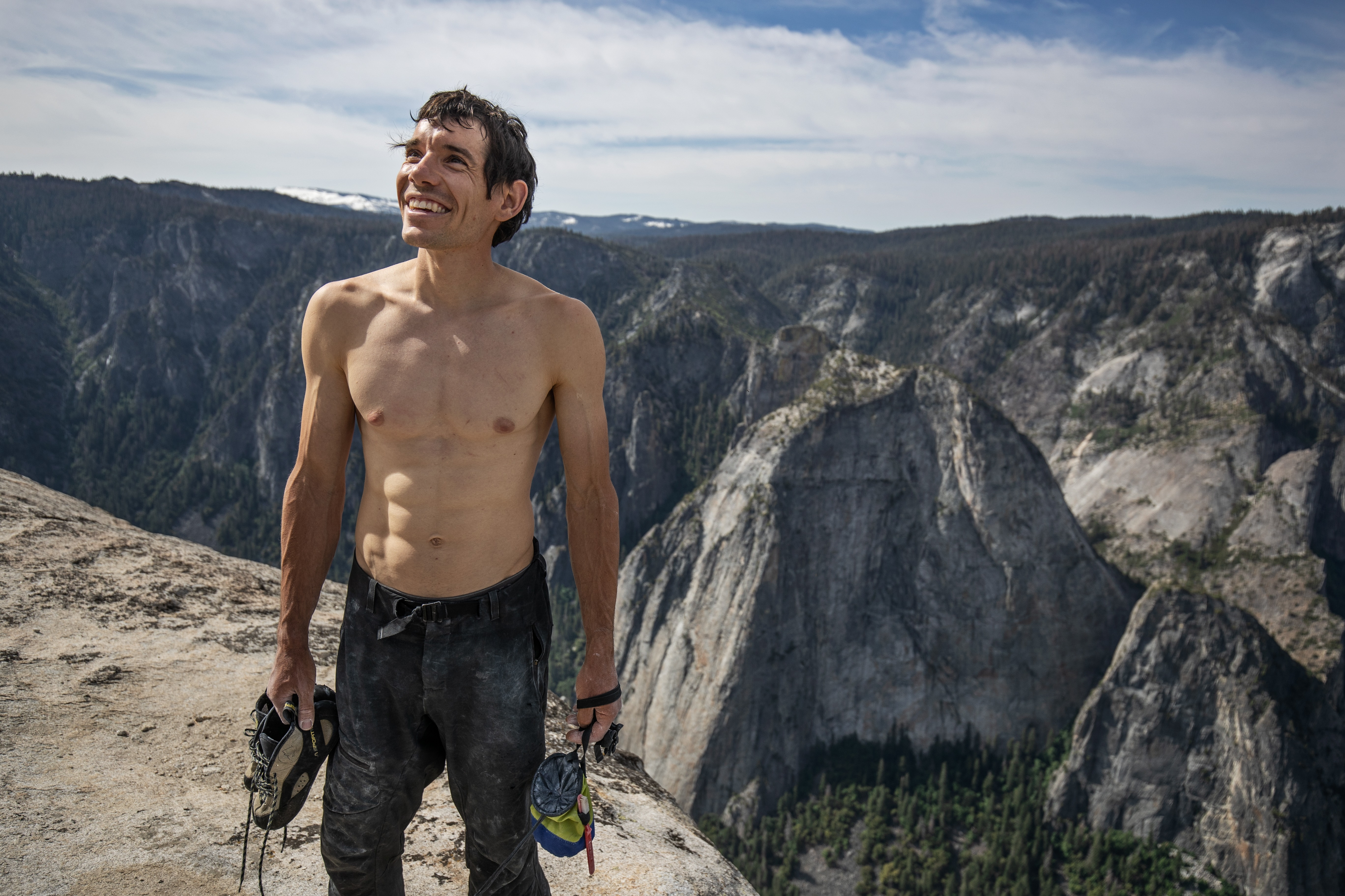Alex Honnold holds all of his climbing gear atop the summit of El Capitan. He just became the first person to climb El Capitan without a rope. (National Geographic/Jimmy Chin)