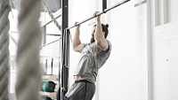 Man doing chin-up in cross training gym