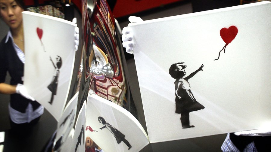 'Balloon Girl' 2003 by artist Banksy is held by Bonham's Andrea Lee and is reflected in a mirror polished vase entiled 'B.O.O.P. by Ron Arad on October 22, 2007 in London. 11 paintings by graffiti artist Banksy are collected here for the first time for a sale called 'Vision 21' on October 24, 2007. (Photo by Peter Macdiarmid/Getty Images)
