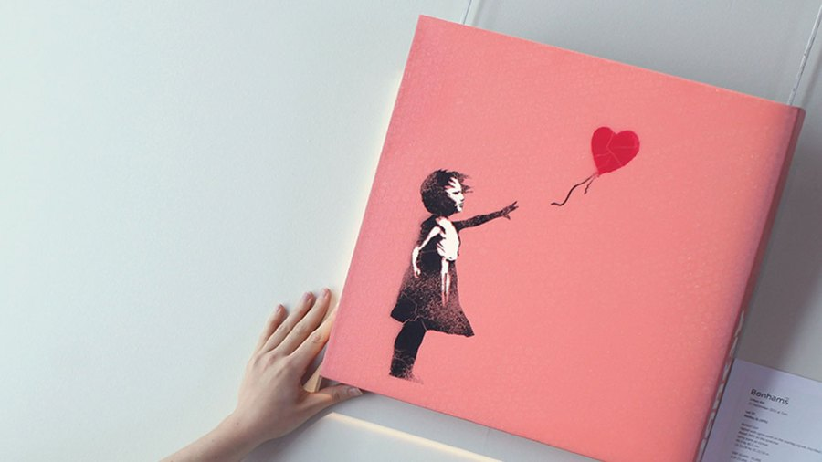 A Bonhams intern poses with a work by Banksy entitled 'Balloon Girl', at Bonhams Auction house on September 16, 2011 in London, England. The piece makes up part of the 'Urban Art' sale which takes place on September 21, 2001 at Bonhams Auction house in London. (Photo by Dan Kitwood/Getty Images)