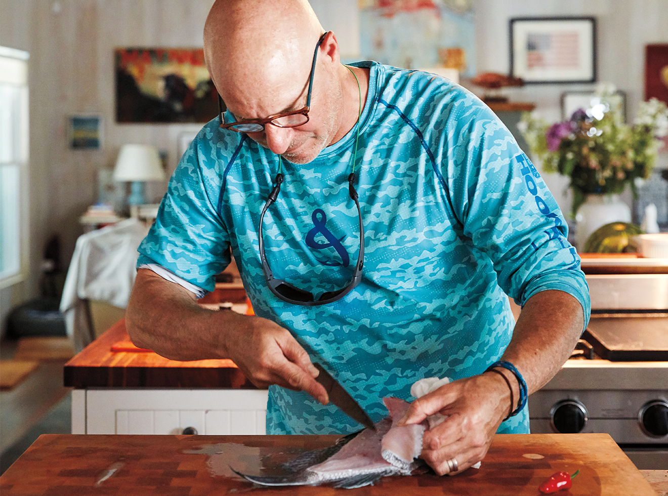 Colicchio, in his kitchen, filleting a black sea bass he caught that morning.