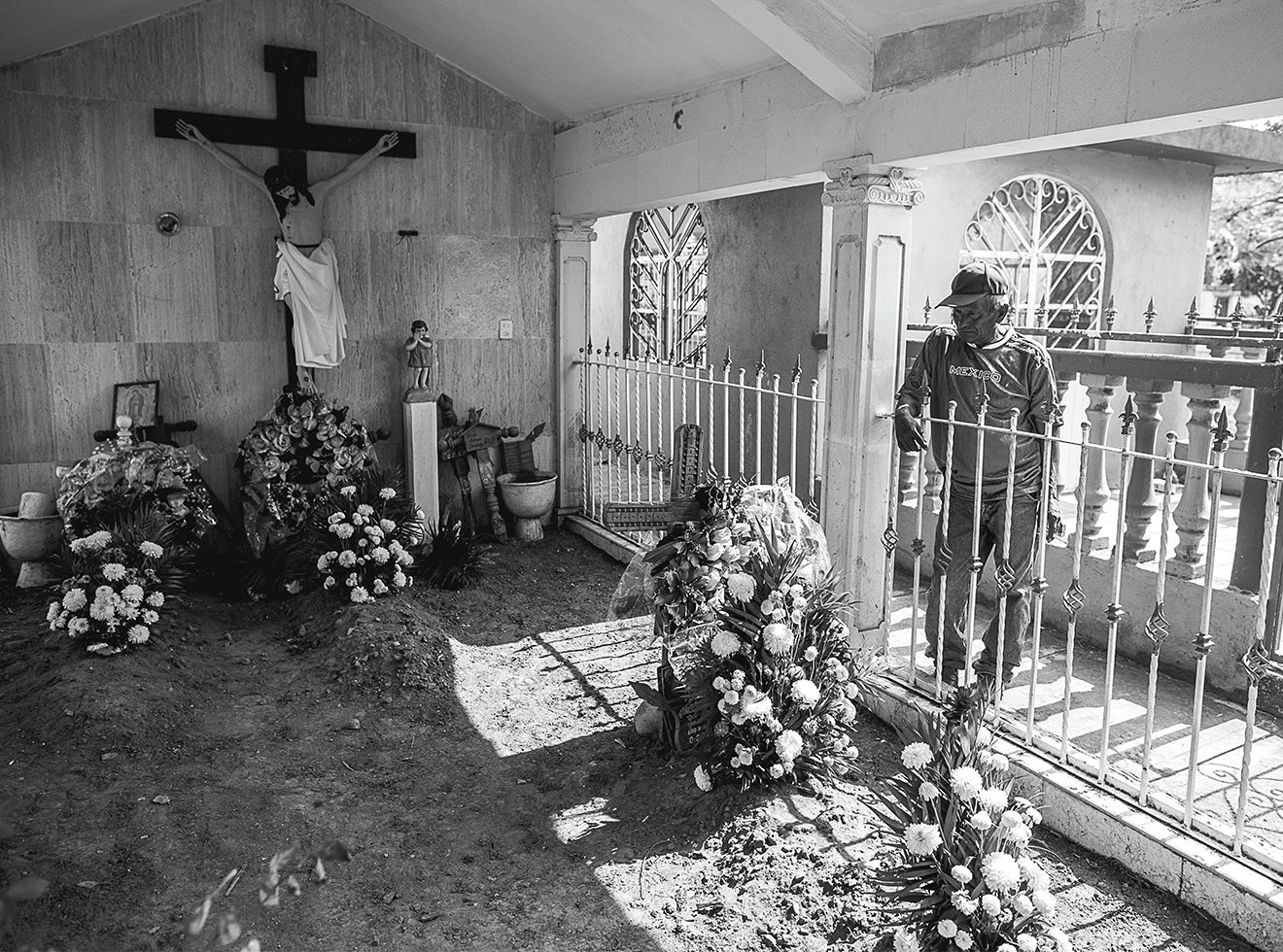 Contreras stops by the tomb of Octavio Colorado Mora, a mechanic whose body he found at a mass-burial site.