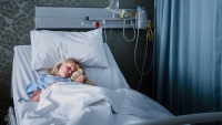 Little girl and a teddy bear in a hospital bed.