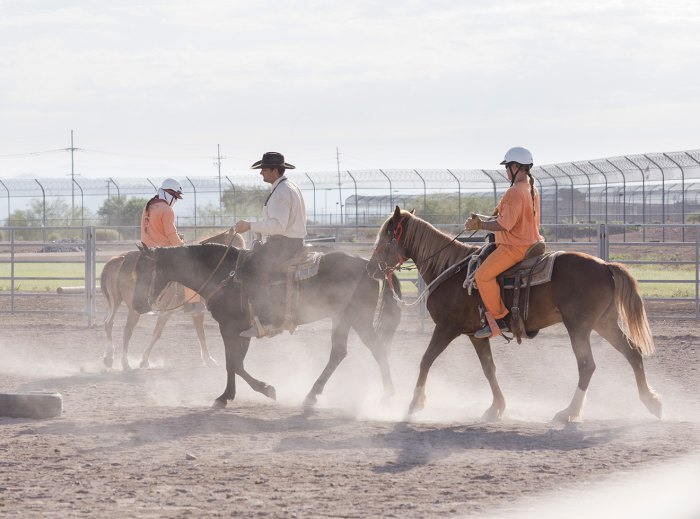 Two inmates ride in a prison corral.