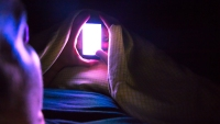 Man checking smartphone at late night inside bed with bright light from point of view.