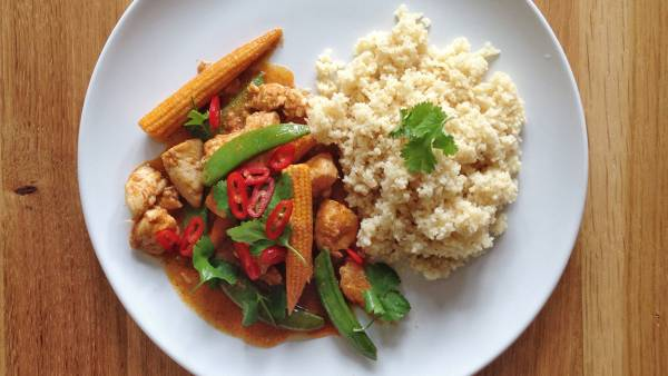Overhead view of stir fried spicy chicken with baby corns and snow peas serves with cauliflower rice
