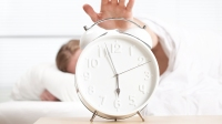 Sleeping man trying to turn off alarm clock. selective focus on the white alarm clock.