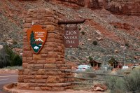 Cars drive through an entrance of Zion National Park, Utah, on February 9, 2017. / AFP PHOTO / RHONA WISE (Photo credit should read RHONA WISE/AFP/Getty Images)