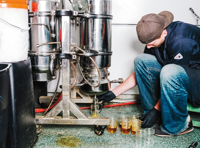 A lab tech collects concentrate from Green Dot's extraction machine.