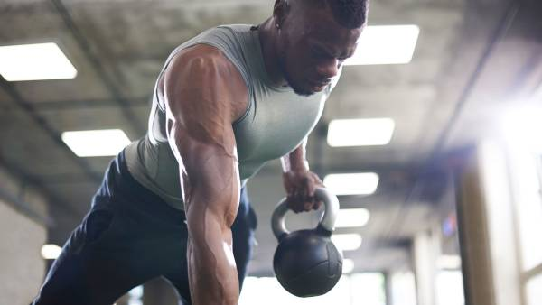 Muscular man doing renegade rows with kettlebell in gym