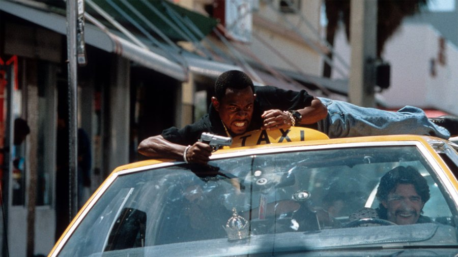 Martin Lawrence rides the roof of a taxi and aims at a scene from the movie