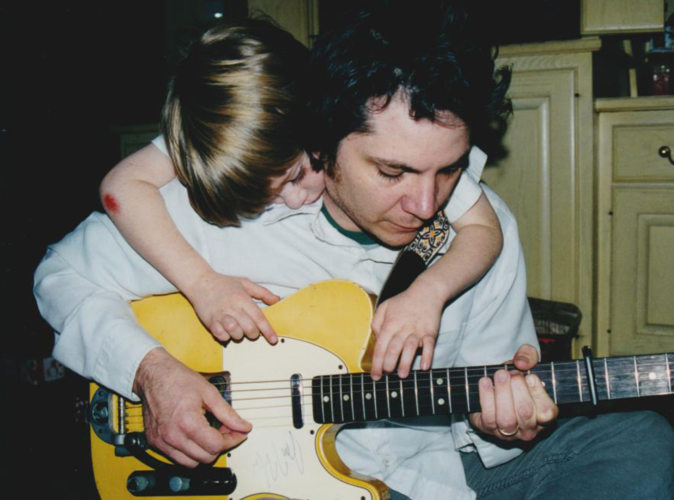 Tweedy picks a Telecaster as his oldest son, Spencer—now 23 and a drummer who recorded the 2014 album Sukierae with his dad—watches.