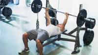 Man doing barbell bench press with chains