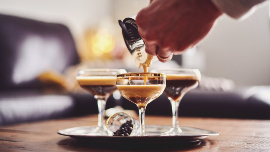 Man pouring espresso martini cocktails at home
