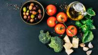 Mediterranean diet foods, including tomatoes, broccoli, garlic, basil, parmesan cheese, and spices