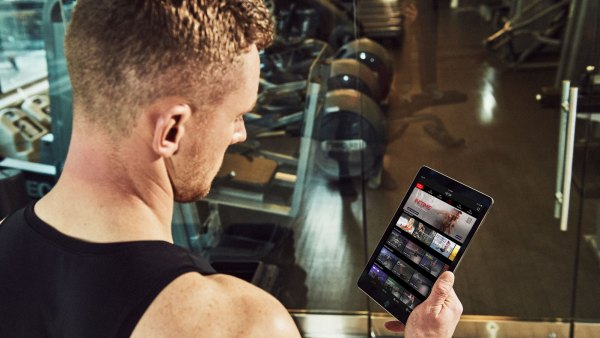 Man using NEOU Fitness app to stream workout