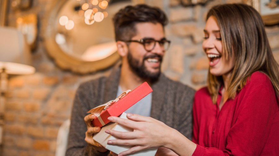 Young woman receiving Valentine's Day gift from her boyfriend