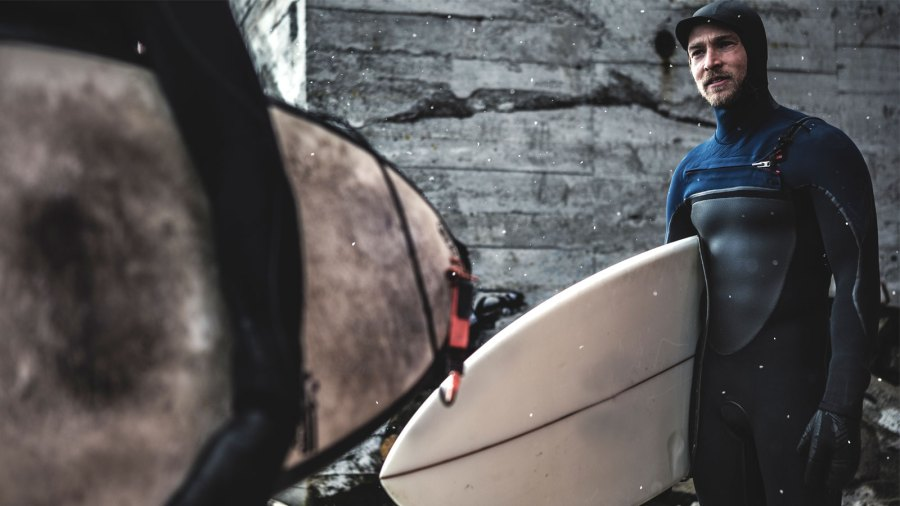 A surfer wearing a wetsuit standing by a wooden building carrying a surfboard.