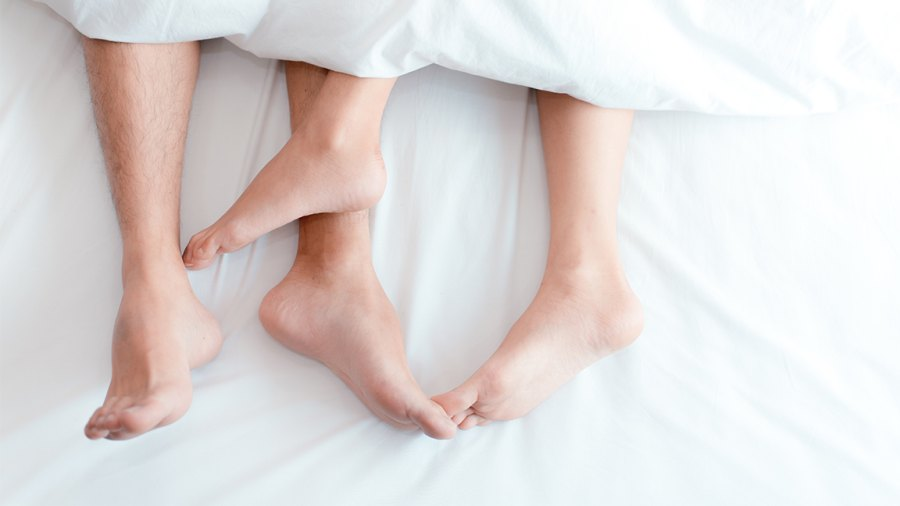 Low Section Of Couple Relaxing On Bed