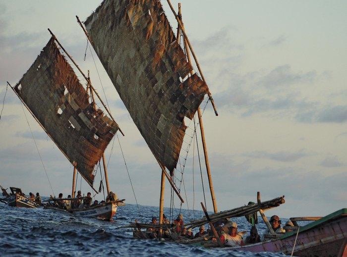 The fleet heads home after a hunt, aboard boats powered by sails crafted from dried palm leaves.