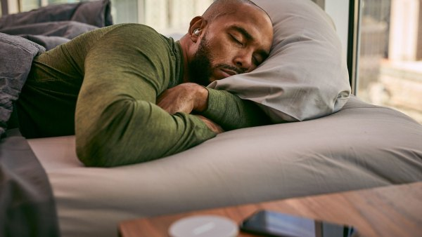 Man sleeping with Bose noise-masking sleepbuds