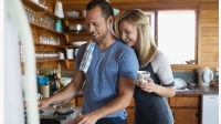 Young couple cooking breakfast in cabin kitchen