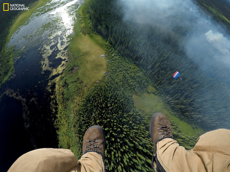 Matt Oakleaf, camera mounted on his gear bag, drops behind the rest of his team to a landing site near smoldering boreal forest. Jumpers can put on 100 pounds of gear and get on a plane in minutes. Their mission: extinguish fires before they rage out of control. (Photograph by Mark Thiessen / National Geographic)