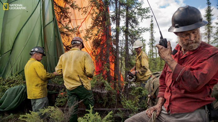 Incident commander Ty Humphrey communicates with a pilot who has dropped a pallet of cargo near a fire. Crew members free the chute from the tree where the load landed. (Photograph by Mark Thiessen / National Geographic)