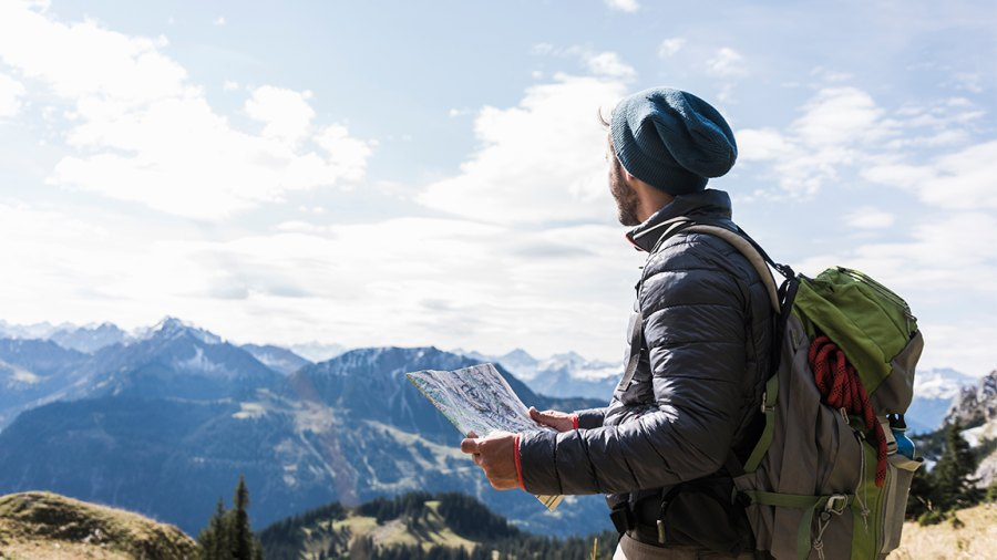 young man with map in mountainscape