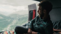 Man sitting in camper van and looking at view of Furka pass