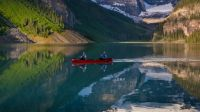 Two people paddle a red kayak across a reflective Lake Louise on June 27, 2013 in Lake Louise, Alberta, Canada. Major flooding along the Bow River in June washed out the Trans-Canada Highway 1 for nearly a week, forcing park visitors to cancel their vacation plans. (Photo by George Rose/Getty Images)