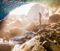A man stands at the entrance of an ice cave bathed in warm sunlight and mist, Wrangell-St. Elias National Park