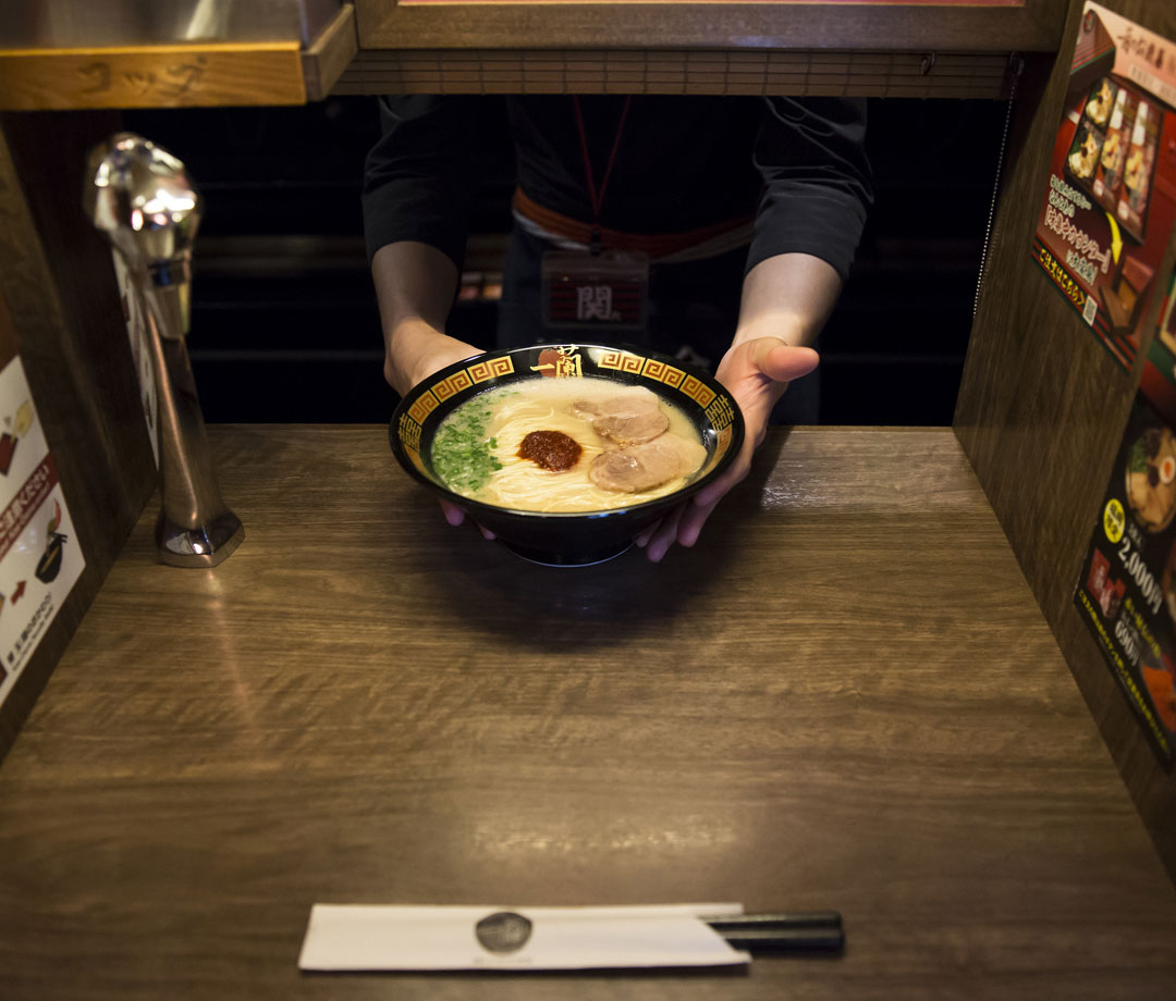 An employee serves a bowl of tonkotsu ramen at Ichiran restaurant in Fukuoka