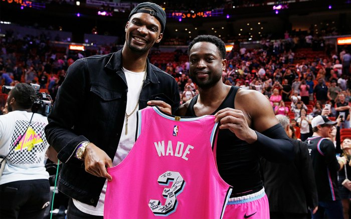 Dwyane Wade #3 of the Miami Heat greets former Miami Heat teammate Chris Bosh with a jersey after the game against the Cleveland Cavaliers at American Airlines Arena on December 28, 2018 in Miami, Florida