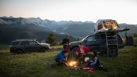 Friends camping, enjoying campfire on remote mountain hilltop, Alberta, Canada
