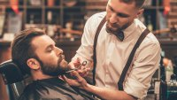 Barber shaping man's beard