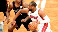 Dwyane Wade #3 of the Miami Heat dribbles the ball against Treveon Graham #21 of the Brooklyn Nets