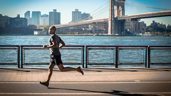 Man running along waterfront, New York, USA