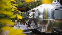 Man standing outside of AutoCamp Airstream