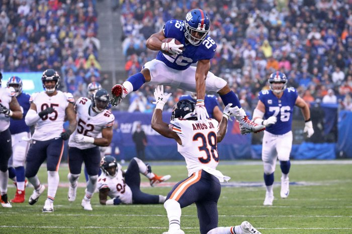 EAST RUTHERFORD, NEW JERSEY - DECEMBER 02: Saquon Barkley #26 of the New York Giants leaps over Adrian Amos #38 of the Chicago Bears for extra yardage during the third quarter at MetLife Stadium on December 02, 2018 in East Rutherford, New Jersey. (Photo by Al Bello/Getty Images)