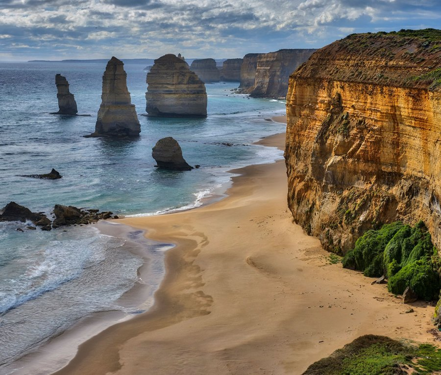 View towards The Twelve Apostles. The Twelve Apostles is a collection of limestone stacks off the shore of the Port Campbell National Park, by the Great Ocean Road in Victoria, Australia.