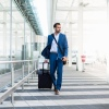 Businessman with trolley and smartphone at airport