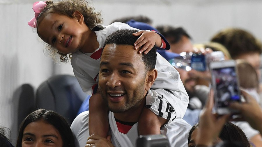 US singer John Legend and daughter Luna watch the International Women's friendly football match between the US and Belgium at the Banc of California Stadium in Los Angeles on April 7, 2019. (Photo by Mark RALSTON / AFP) (Photo credit should read MARK RALSTON/AFP/Getty Images)